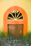 The little door in a yellow wall and green grass Stock Image