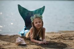 Little mermaid on the beach. The little dream mermaid girl on the beach stock image