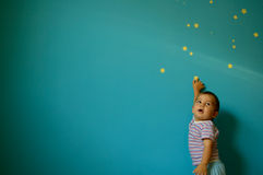Little Dreamer. Child pointing to a star from a nice blue wall. He indicates the place where he want to be in the future royalty free stock image