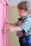 Little dreaming boy opens pink door Royalty Free Stock Photography