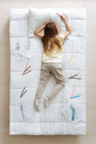 Little dressmaker falling asleep in her bed Stock Photography