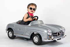 Little driving girl. Small girl drives with sun glass in a toy car laughing Royalty Free Stock Photo