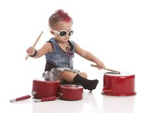 Little Drummer. Adorable toddler dressed as a rock star with a pink Mohawk and banging on pots and pans with drum sticks Stock Images