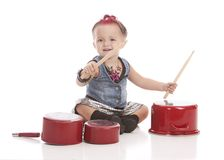 Little Drummer. Adorable toddler dressed as a rock star with a pink Mohawk and banging on pots and pans with drum sticks Stock Photography