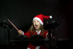 Little drummer disguised as Santa Claus playing the elettronic drum kit Stock Image