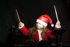 Little drummer disguised as Santa Claus playing the elettronic drum kit Stock Photos