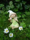 Little dwarf girl with a bird in her hand sits on a green meadow Stock Photos