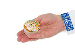 Little Easter cake in male hand on a light background Royalty Free Stock Photos