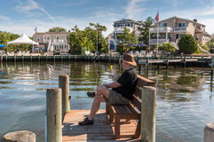 Little Egg Harbor, Long Beach Island, NJ, USA. Man seated on bench on the dock, looking out into Little Egg Harbor Royalty Free Stock Images