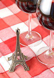 Little Eiffel tower and a pair of wineglasses. On the table Royalty Free Stock Images