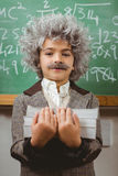 Little Einstein holding books in front of chalkboard Stock Photo