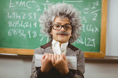 Little Einstein holding books in front of chalkboard Royalty Free Stock Images