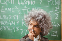 Little Einstein thinking in front of chalkboard Royalty Free Stock Image