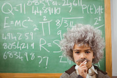 Little Einstein thinking in front of chalkboard Royalty Free Stock Photo