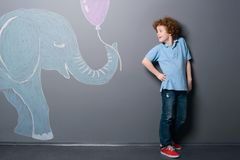Little elephant gives a balloon. To shy boy. Young guy standing with arm on hip and looking at the animal with a gift depicted with chalk on a gray wall stock photos