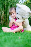 Little elfin girl sittinging in the grass with large teddy bear Royalty Free Stock Photography