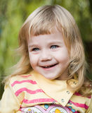 Little emotional girl in a green garden. Royalty Free Stock Images