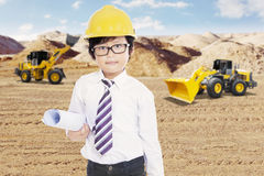 Little engineer and excavator in mining site Stock Image