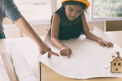 Little engineer girl in the safety helmet with a construction bl Stock Photography