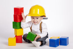 Little engineer plays with cubes Stock Photo