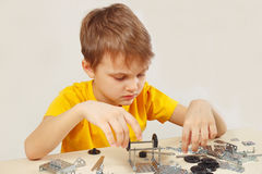 Little engineer plays with mechanical starter kit at table Royalty Free Stock Photography