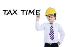 Little entrepreneur writes tax time. Cute little businessman with helmet writes tax time on whiteboard, isolated over white Stock Photo