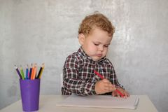 Little European boy draws with colored pencils stock photos