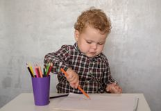 Little European boy draws with colored pencils stock images