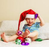 The little European boy with toys on a bed. Royalty Free Stock Photography