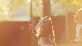 Little European children are jumping and playing with the soap bubbles in a sunset light. Lens flare, outside shooting