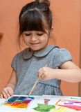 Little european girl painting at table indoors. royalty free stock photography