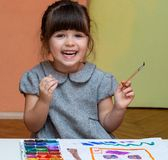 Little european girl painting at table indoors. stock image