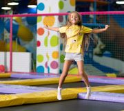 Little excited girl photographed at the jump on the trampoline. Little excited girl in a yellow T shirt jumping on the trampoline on the colorful amusement park stock photography