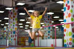 Little excited girl photographed at the jump on the trampoline. Little excited girl in a yellow T shirt jumping on the trampoline on the colorful amusement park stock image