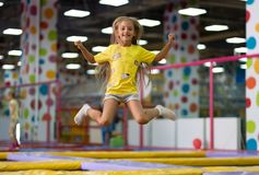 Little excited girl photographed at the jump on the trampoline. Little excited girl in a yellow T shirt jumping on the trampoline on the colorful amusement park stock photos