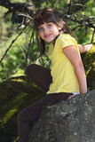 Little explorer girl climbing. A happy little girl with dark hair and yellow shirt exploring and climbing rocks in the woods. Shallow depth of field Stock Photos
