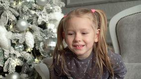The little fair-haired girl smiles sitting on a sofa at a New Year tree. Slow mothion. The little fair-haired girl with tails considers toys on a Christmas tree stock video