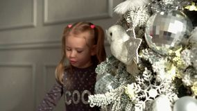 The girl plays near a New Year tree with a white feather. The little fair-haired girl with tails considers toys on a Christmas tree. The lovely girl plays near stock video footage