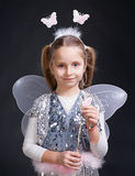 Little fairy. Happy little girl dressed up as a fairy on a gray background Stock Photography
