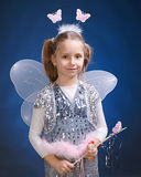 Little fairy. Little girl dressed up as a fairy on a blue background Royalty Free Stock Image