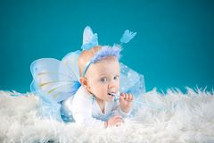 Little fairy. Cute baby girl on blue background Stock Photo