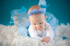 Little fairy. Cute baby girl on blue background Royalty Free Stock Photo