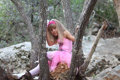 Little fairy ballerina lost in a forest. Five years old girl fairy ballerina sitting alone on a stone in a forest among trees Royalty Free Stock Images