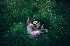 Little fairy. Girl like a fairy sitting in grass meadow  hugs lost dog shot from above Royalty Free Stock Images