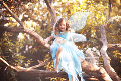 Little fairy. Girl sitting on a tree in the fairy forest Stock Photo