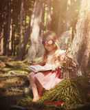 Little Fairy Girl in Woods Reading Book. A little girl is wearing white sparkle fairy wings outside in the woods reading a fairy tale book for an education or stock images