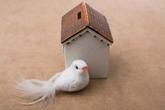 Fake bird  behind a model house Royalty Free Stock Photos