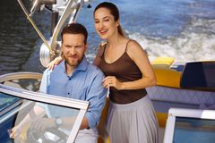Pleasant young couple enjoying sailing on motorboat. Little family adventure. Pleasant young couple sailing a motorboat and smiling while observing the river in royalty free stock photos