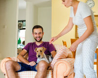 Little family and dog. Man and women in they house playing with the dog Royalty Free Stock Image