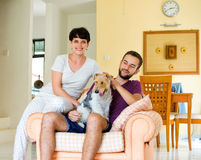 Little family and dog. Man and women in they house playing with the dog Stock Photography